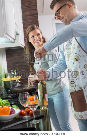 Man opening wine bottle while cooking with woman in kitchen - Stock Photo