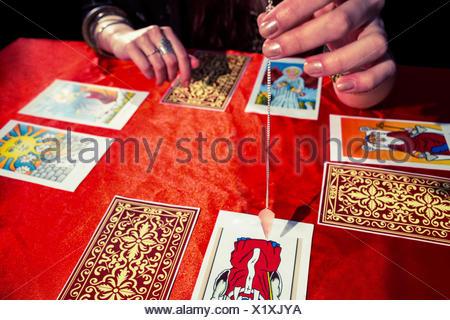 Cropped image of fortune teller using pendulum - Stock Photo