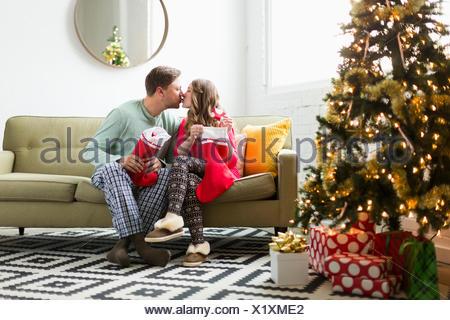 Young couple with Christmas stockings kissing on sofa - Stock Photo