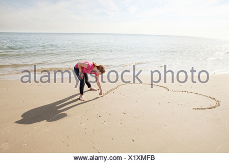 Teenager draws heart in sand on beach - Stock Photo