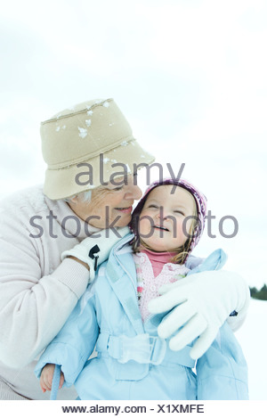 Grandmother embracing toddler in snow, both smiling - Stock Photo