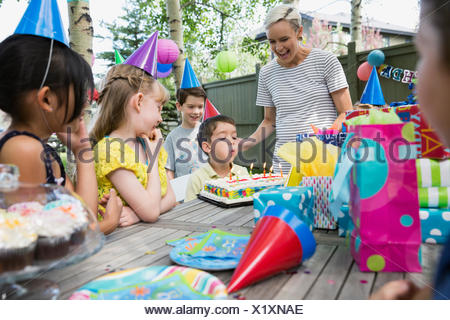 Mother friends watching boy blow out birthday candles - Stock Photo