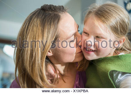 Mother kissing her daughter - Stock Photo