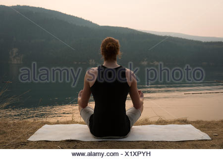 Fit woman sitting in meditating posture on an open ground - Stock Photo