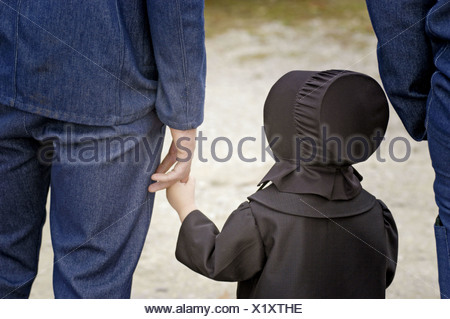 Amish of the American Heartland:  Ohio, Indiana, Pennsylvania. Family at market, dad and daughter holding hands. - Stock Photo