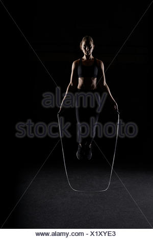 Woman skipping in gym - Stock Photo