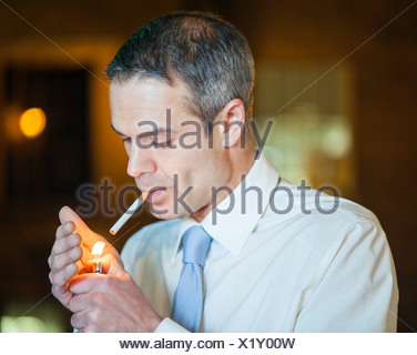 MODEL RELEASED Man lighting a cigarette - Stock Photo