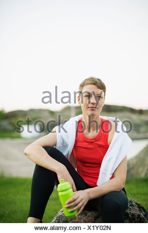 Portrait of sporty woman with water bottle and towel relaxing on rock - Stock Photo