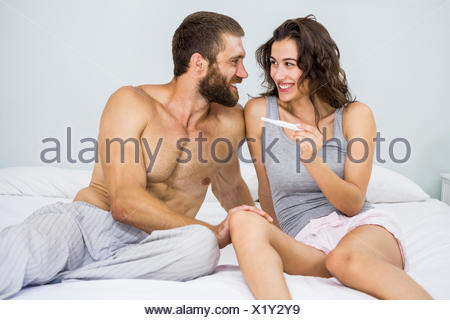 Happy couple looking at pregnancy test on bed - Stock Photo