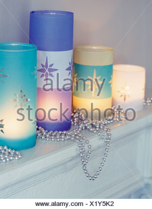 Close-up of etched glass candle holders with lighted candles - Stock Photo