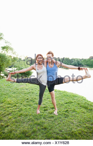 Couple practicing yoga by water - Stock Photo