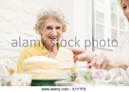 Senior woman and daughter, slicing cake - Stock Photo