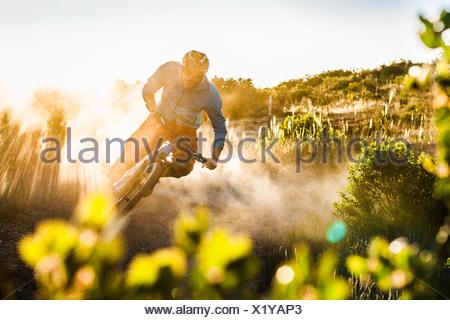 Young man mountain biking, Monterey, California, USA - Stock Photo