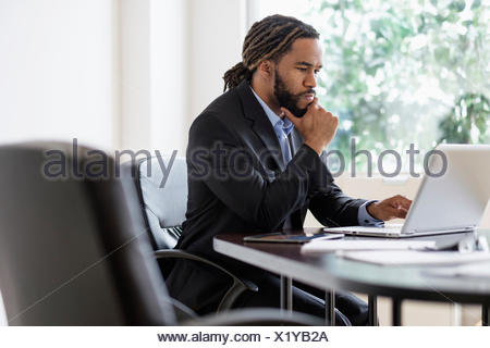 Concentrated businessman working with laptop at desk in office - Stock Photo