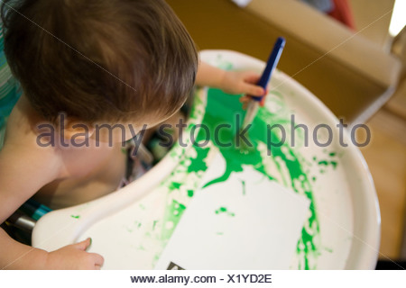 Baby boy in high chair with green paint - Stock Photo