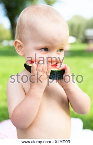 Baby, 12-14 months, eating watermelon - Stock Photo