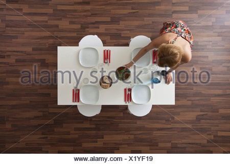 Woman setting dining room table for dinner party, overhead view - Stock Photo