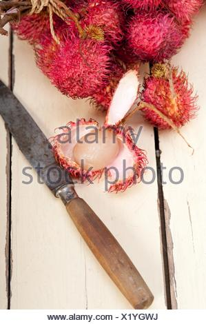 fresh tropical rambutan fruits over rustic wood table. - Stock Photo