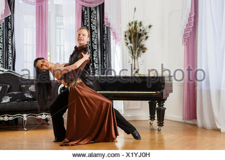 Dancing young couple in the room. - Stock Photo