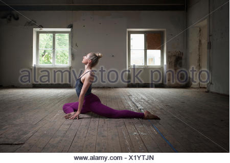 Mid adult woman practicing pigeon pose in yoga studio, Munich, Bavaria, Germany - Stock Photo
