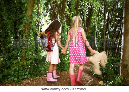 Rear view of two girls carrying teddy bear and backpack walking in forest - Stock Photo