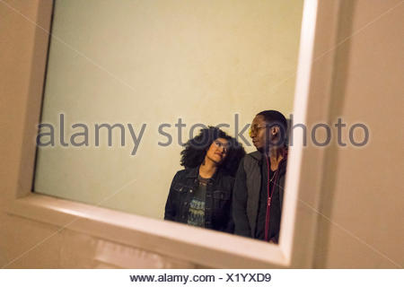 View through glass pane in door of couple - Stock Photo