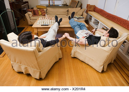 Couple relaxing at home in living room - Stock Photo
