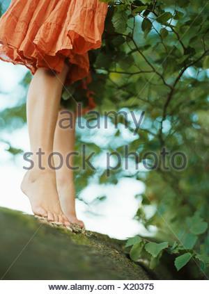 Girl standing barefoot on a log - Stock Photo
