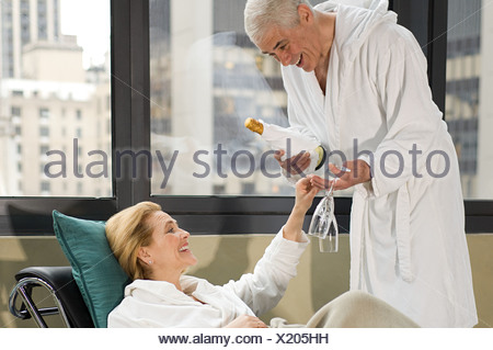 Senior couple drinking champagne in bathrobes - Stock Photo