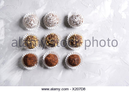 Variety of homemade dark chocolate truffles with cocoa powder, coconut, walnuts in row over gray texture background. Top view, copy space. - Stock Photo