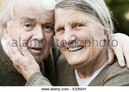 Portrait of smiling senior couple head to head - Stock Photo