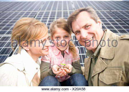 Family posing together front solar panels Munich, Bavaria, Germany - Stock Photo