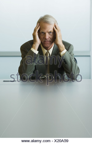Businessman sitting with head in hands, looking at camera - Stock Photo