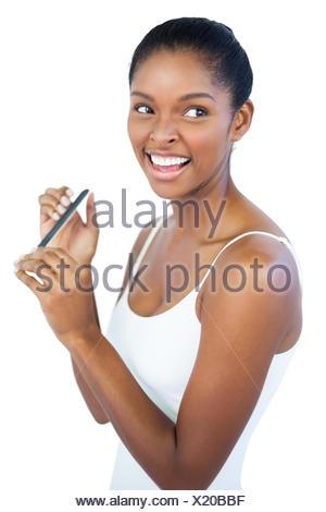 Smiling woman using nail file on white background - Stock Photo