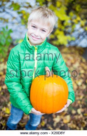 MODEL RELEASED. Blonde boy holding pumpkin in park, portrait, smiling. - Stock Photo
