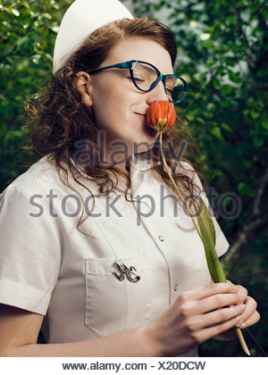 Nurse in glasses smelling flower - Stock Photo