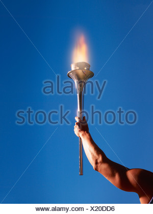 Athlete's arm holding up a torch - Stock Photo