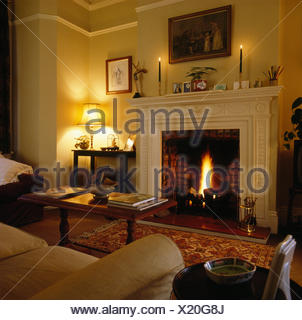 Lighted fire in fireplace in eighties living room with lighted lamp and candles - Stock Photo