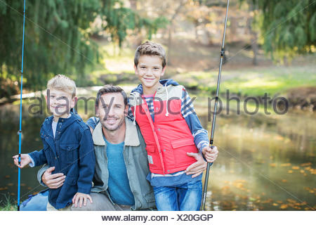 Portrait smiling father and sons with fishing rods - Stock Photo