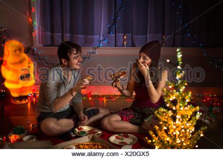 Young couple enjoying pizza at christmas - Stock Photo