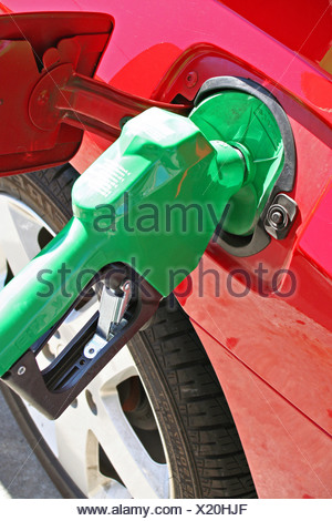 Bright green gas pump in red car - Stock Photo