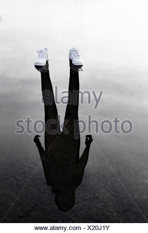 Reflection of a sportsperson wearing trainers - Stock Photo