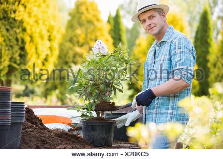 Portrait of confident man planting pot at garden - Stock Photo