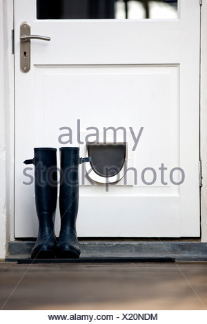 A pair of Wellington boots by a door - Stock Photo