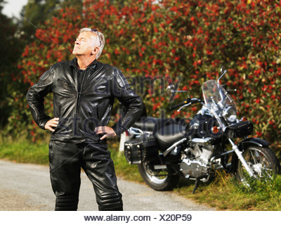 Older man in leather with motorcycle - Stock Photo