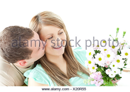 Enamored man giving a bouquet to his girlfriend - Stock Photo