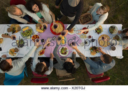 Overhead view friends toasting wine glasses at garden party dinner - Stock Photo