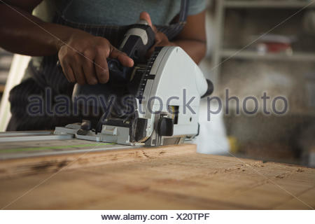 Mid section of carpenter leveling wood - Stock Photo