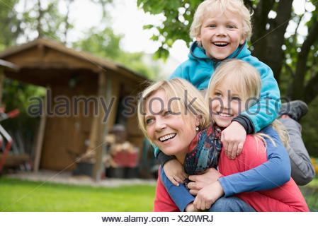 Mother playing garden with young kids piggyback - Stock Photo