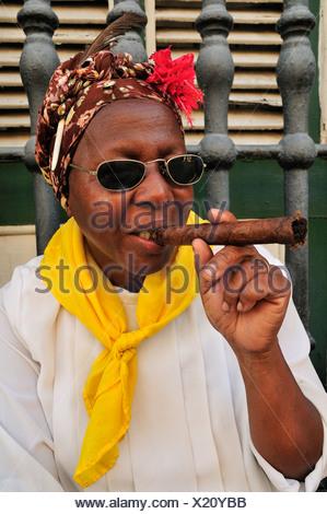 Cuban woman with a cigar in Old Havana, Habana Vieja, Havana, Cuba, Caribbean - Stock Photo